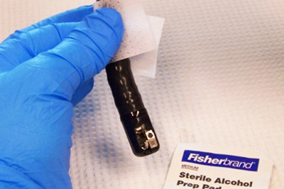 Image of blue gloved hand disinfecting a duodenoscope with an alcohol prep pad.