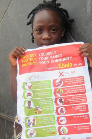 Image of a young girl holds a poster about Ebola protection