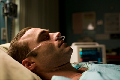 Image of a patient lying in bed asleep with a monitor in the background