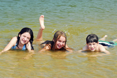 image of three children laying in a shallow area of a body of water and smiling at the camera