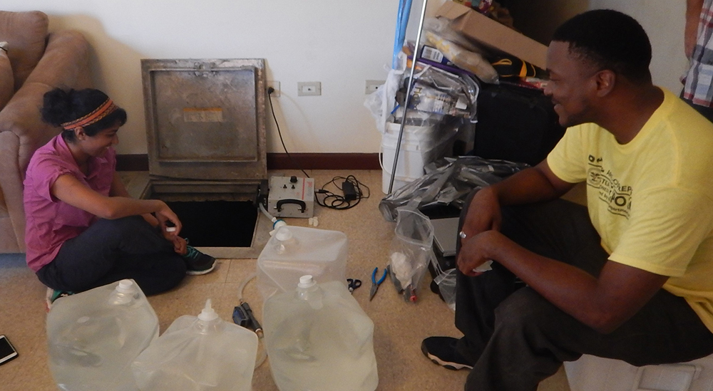 Gouthami Rao (DFWED) and Kaunda Williams (VIDOH) oversee the collection of a water sample from a household cistern to test for evidence of waterborne pathogens.
