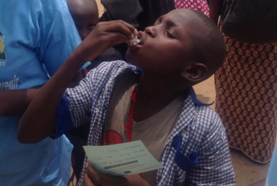 Young boy drinking a cholera vaccine from a small bottle