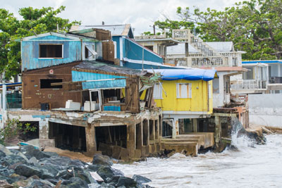 Brightly colored home is battered by winds and waves