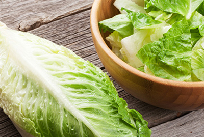 head of romaine lettuce next to a bowl full of chopped romaine lettuce