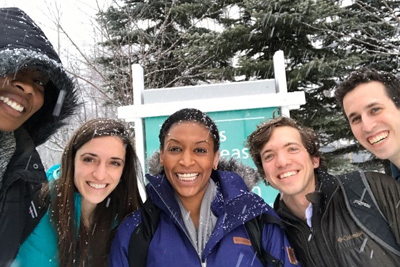 Group of young scientists bundled in winter geer but smiling at the camera while snow falls