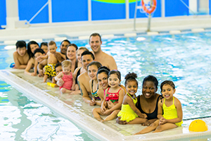 An image of a long float in a pool with children sitting in a line. In the water next to the children stands two instructors.