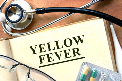 "A stethoscope, glasses and capsules surrounding a page with the words ""Yellow Fever."""