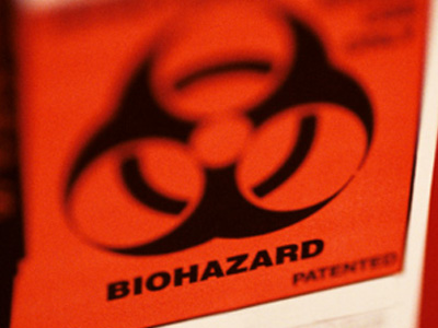 An orange biohazard label on a bright red container.