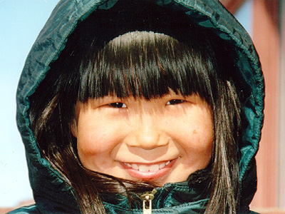 Young Alaskan girl in warm green hooded parka