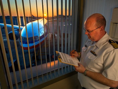Airport offical reviews a checklist on a clipboard next to a window. Outside the window there is commercial airplane in front of a setting sun.
