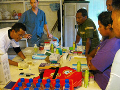 CDC responded to an outbreak of dengue in the Marshall Islands. This image shows a group of people standing around a table full of equipment, watching a demonstration for a rapid diagnostic test that detects the presence of dengue virus in people with dengue-like symptoms.