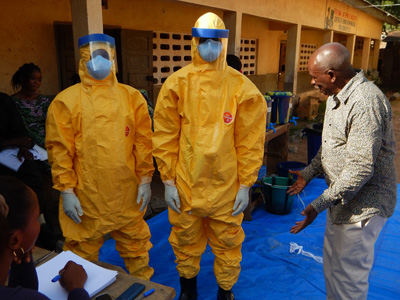 Training is provided for Red Cross volunteers during the Ebola response. Here, Guinean Professor Lamine Koivogui, is doing hands-on training with two individuals in yellow protective gear.