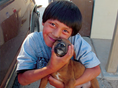 A smiling boy holding a little brown puppy