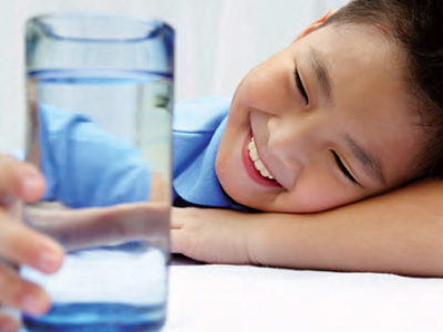 A young boy in a blue shirt sits at a white table, laying his head on his arm, smiling at a clear glass of water in his hand.