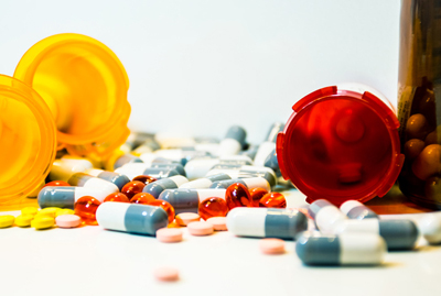 image of several prescription bottles and spilled pills on a white background