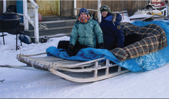 CDC scientists in heavy coats sitting with their equipment on a dog sled