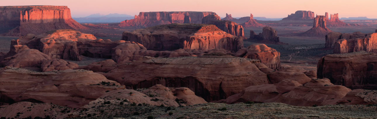 Wide panoramic shot of colorful canyons in the southwest as the sun sets