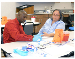 Figure 3. Participants in a rapid HIV testing training session; This photo shows a man and a woman participating in a training session for rapid HIV testing.
