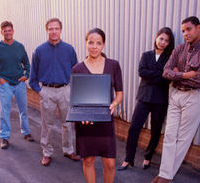 Group of men and women standing together around a laptop computer