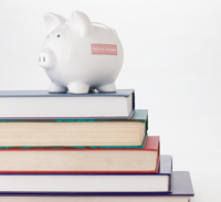 Photo of piggy bank sitting on a stack of books