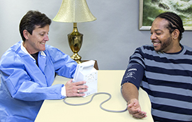 Photo of health technician taking a participant's blood pressure
