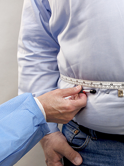 Photo of man's waist being measured with measuring tape