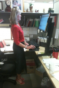 woman standing at a desk workstation