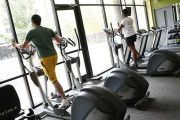 Two people working out on an elliptical