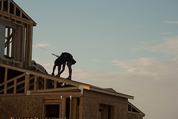 construction worker on a roof at twilight