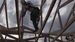 man climbing on a roof frame