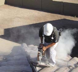 Worker creating a large cloud of dust while cutting