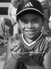 a hispanic boy on a farm holding a small animal