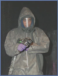 Worker wearing face mask, protective suit and gloves.