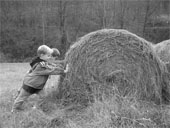 two children pushing against a round bale of hay