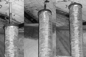 Three black and white pictures of a section of mine ceiling. The ceiling is buttressed by wire mesh and steel angle iron and the pictures are taken from the same position over time. In the foreground of all three pictures is a roof bolting drill bit, surrounded by a collapsible drill steel enclosure(CDSE), as it drills into the mine ceiling. In each picture the CDSE moves closer to the mine ceiling.