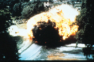 A giant fireball surrounded by Black smoke, followed by red fire and then white fire coming from the direction of several 2 or 3 story buildings nestled into trees.