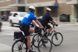 Two police officers on mountain bikes on a city street riding away and to the right of the camera. The background is dominated by a brick building with several large windows and entrances. They are crossing traffic and you can see a white SUV heading in their direction between them and the building.