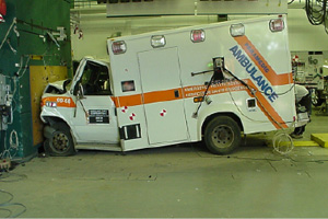 This picture is set inside an industrial looking space with concrete floor and wires and equipment attached to the walls. In the background you can see a pegboard wall with tool neatly arranged on it. In the foreground is an ambulance which has crashed head-first into a wall at the spot where there is a reddish brown plate just a little bit wider and taller than the grill of the ambulance.