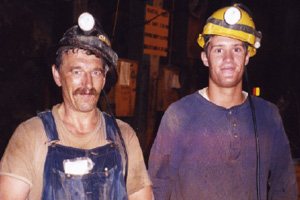 Two men look directly at the camera and grin. They are both very dirty. One man in overalls and t-shirt wearing a black miner's hardhat with a light attached to the front looks to be about 50. Standing very close to this man is a younger man, probably in his twenties. He is wearing a dirty blue shirt and a yellow miner's hard hat with a light attached to the front and a smaller one just above his right ear.