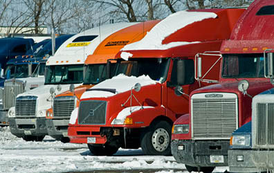 This photo was taken in the winter. Eight semi-trailers are parked in a row. You see their grills and cabs but not what they are hauling. They are different makes, models, and colors. One red semi in the center of the photo is covered with a file layer of snow. A blue semi has icicles hanging from its grill. The ground in front of them is covered with ice and snow. The trees in the background are barren and the sky is bright blue.