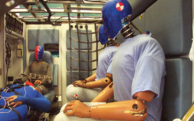 Photo of the inside of an ambulance simulator. 3 crash-test dummies have been positioned sitting upright in the ambulance crew seats. Another dummy lies on a gurney in front of them. The dummy in the foreground has a rip on its elbow from wear and tear. All the dummies and objects are in place and it is clear the crash simulation has not yet happened.