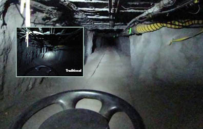 This photo shows a mining tunnel. The ceiling is gridded with what looks like a system of steel pipes and bars. Running along the right side is a yellow tube. The picture is taken from the perspective of a rail car driving down the tracked tunnel—as evidenced by the top third of a steering wheel at the bottom center of the picture. Inset is another picture (labeled before) of the same scene. Most of the ceiling and walls are in complete darkness. One bright spot of light illuminates a small part of the tunnel directly in from of the rail car.