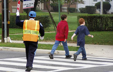 In this photo a woman in a blue uniform stands in the middle of a street crosswalk. She wears an orange and yellow pinafore with the words crossing guard written on it in large black letters. She is holding a stop sign in her left hand. 2 adolescent boys cross the street in front of her.