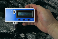 Photo of a Coal Dust Explosibilty Meter (CDEM). Held within a person's hand and in a mine, demonstrating the real-time operability of the CDEM. The CDEM is indicating Green, Test Complete.