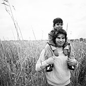 Man in crop field with young boy on his shoulders.