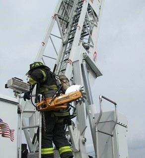 A fire chief demonstrates the challenges in accessing an aerial ladder and truck steps.