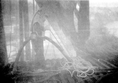 Figure 1. Construction worker using a HEPA-filter vacuum inside a containment structure. Note that the worker is obscured by a high airborne concentration of dust