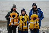 The three crew members of the setnet skiff Paul Revere posing on the shore of Bristol Bay, Alaska with the inflatable personal flotation devices that saved their lives.