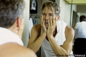 a man looking in the mirror with his hands on his face