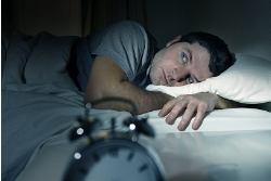 man lying in bed wide awake